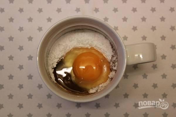 1. В высокую кружку, которую можно ставить в микроволновку, всыпьте сахарную пудру и какао, добавьте яйцо и пару капель ванильного экстракта.