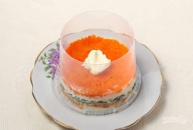Почистите и вымойте морковь. В отдельной кастрюле закипятите воду и отварите в ней морковь до готовности. Затем натрите морковь на терке и выложите слой в салат. Смажьте слой майонезом.