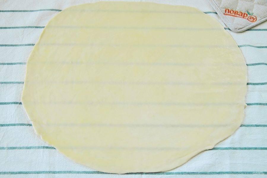 Чистое кухонное полотенце слегка припылите мукой и раскатайте на нем тесто в виде большого прямоугольника до прозрачного состояния.