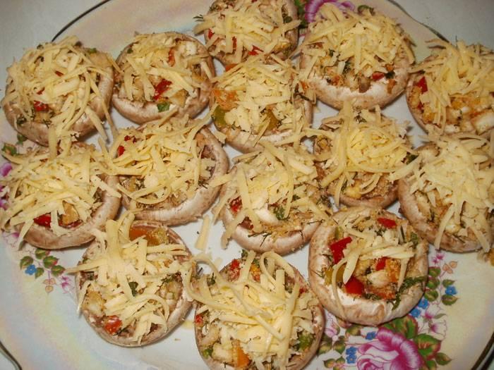 3. Выкладываем в чашечки грибов, и посыпаем тертым сыром.