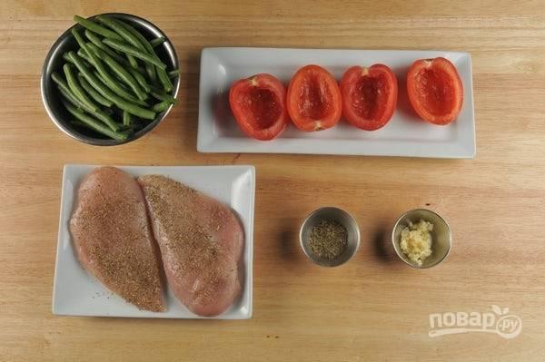 1. Фасоль разделите пополам. Помидоры разрежьте на половинки, удалив семена с жидкой мякотью. Грудку смажьте травами, перцем и солью. Чеснок измельчите.
