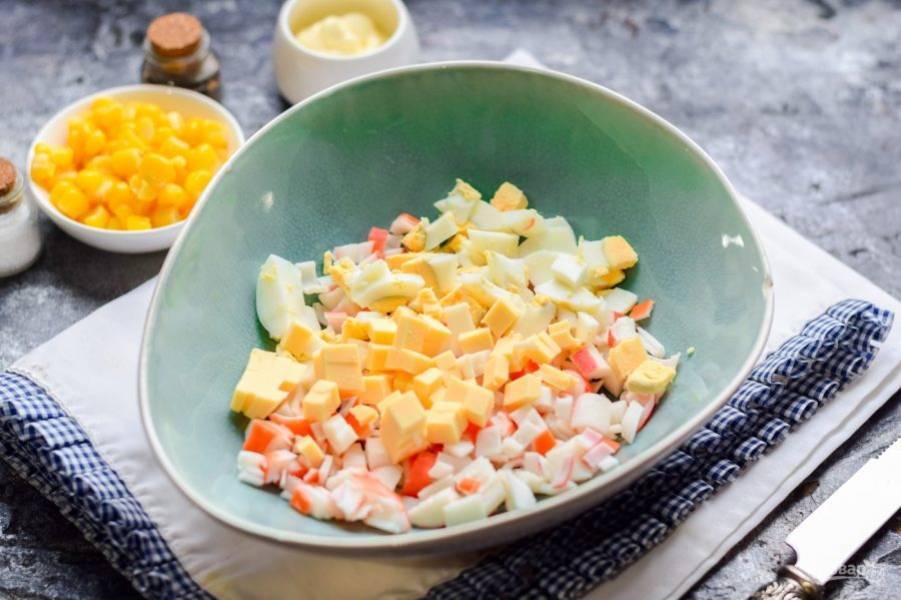 Твердый сыр и вареное яйцо нарежьте небольшими кубиками, добавьте в салат к палочкам.
