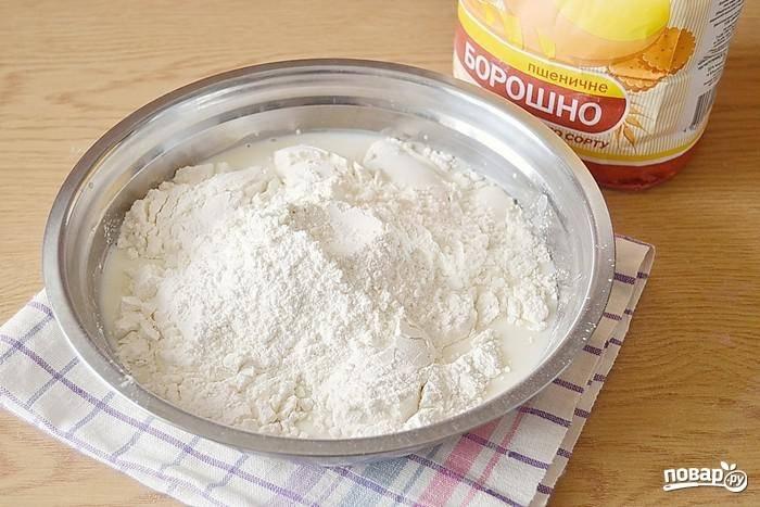 Добавьте примерно половину муки и замесите вязкое тесто.