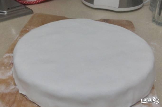 Смачивая края мастики водой, равномерно распределите ее по торту.