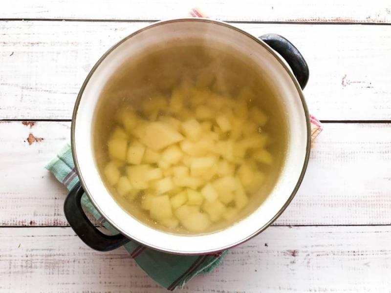Картофель очистите, помойте, нарежьте небольшими кусочками и выложите в куриный бульон. Варите картофель в течение 10-12 минут.