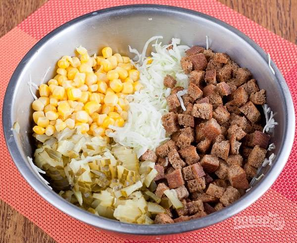 Смешайте в салатнице сухарики, огурцы, капусту и кукурузу.