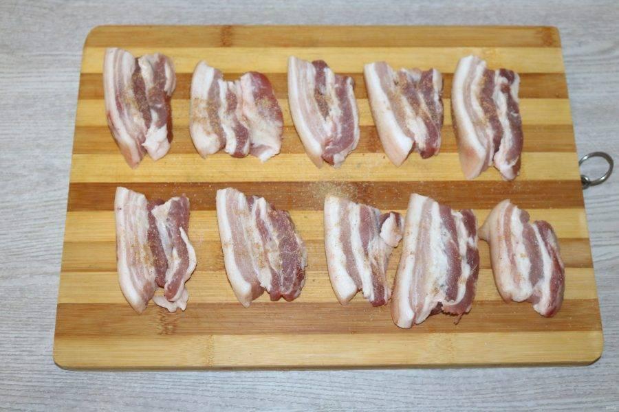 Разложите нарезанные кусочки грудинки. Посолите и посыпьте специями с двух сторон.