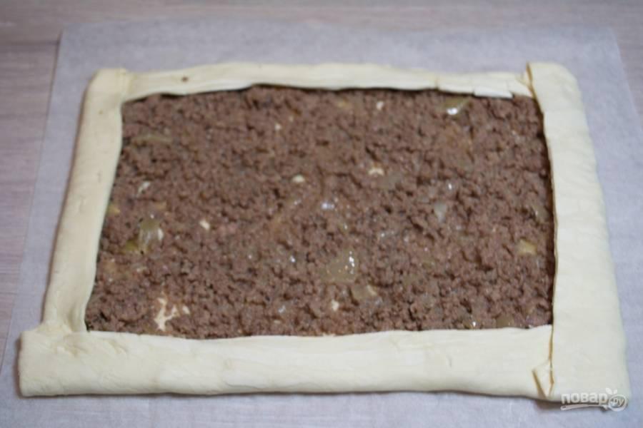 На пласт теста выложите фарш. Распределите его по по поверхности пласта, отступив от края 2-3 см. Поднимите края пласта теста и сформируйте бортики.