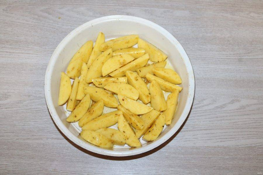 В форму для запекания выложите картофель. При желании форму можно застелить пекарской бумагой.