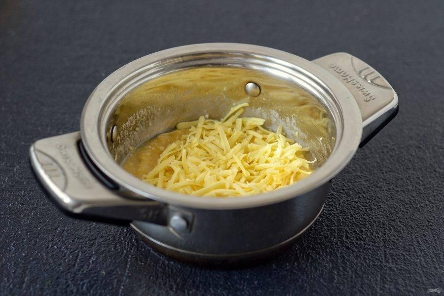 Добавьте тертый сыр. Перемешайте и варите кашу ещё 5 минут, пока сыр полностью не расплавится.