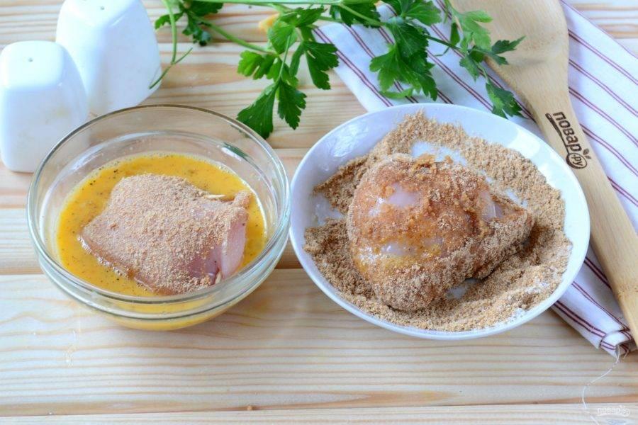 Обваляйте куриные грудки с начинкой сначала в панировочных сухарях, смешанных с солью, затем во взбитом с перцем яйце, а затем снова в панировочных сухарях.