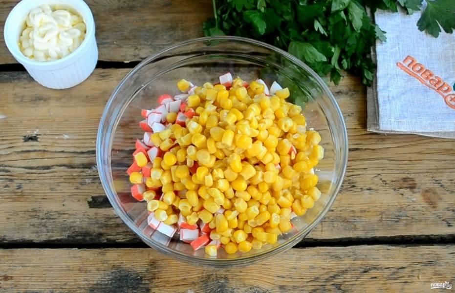 Смешайте яйца и крабовые палочки в глубокой миске, добавьте консервированную кукурузу.