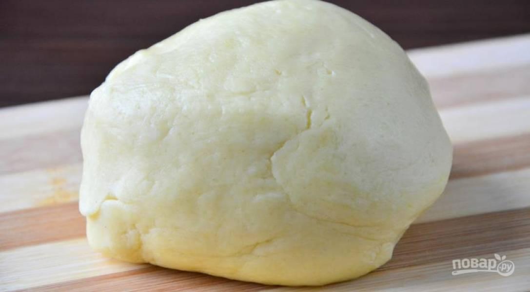 Растопите сливочное масло, добавьте к нему сорок грамм сахара, желтки, соль, воду и просейте муку. Замесите тесто, скатайте в шар и поставьте охлаждаться в холодильник.