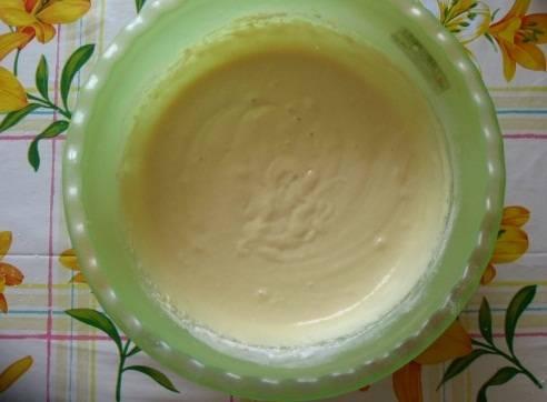 """Замесите тесто: для этого смешайте в большой посуде яйца, кефир, соль. Хорошенько перемешайте, добавьте соду. После этого медленно добавляйте муку, постоянно перемешивая. Если образовались комочки, """"разбейте"""" их, чтобы тесто стало однородным.  По консистенции оно  должно быть похожим на жирную сметану."""