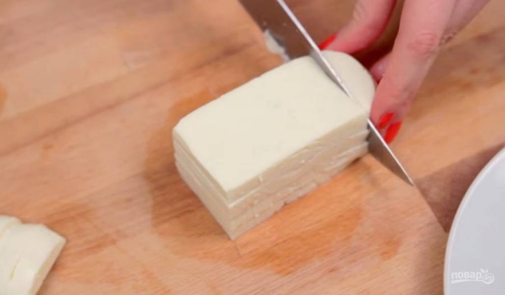 1. Нарежьте адыгейский сыр небольшими кусочками толщиной примерно 1 см. Желательно, чтобы кусочки были одинакового размера и формы, так готовое блюдо будет выглядеть красивее.