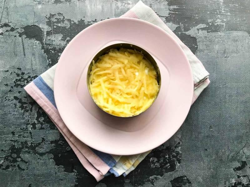 Яблоко хорошо помойте под проточной водой, очистите от шкурки, удалите сердцевину, натрите на средней терке и выложите поверх филе. Смажьте слой из яблок сметаной.