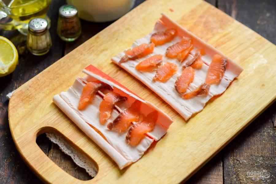 Красную рыбу нарежьте пластинами и выложите на палочки.