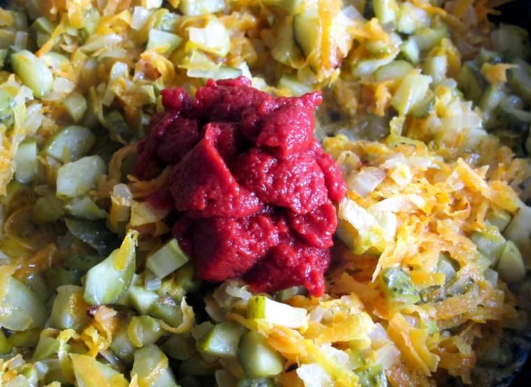 2. На отдельной сковороде обжарим измельченные лук, морковь и соленые огурцы. Сюда же добавим томатную пасту и специи по вкусу.