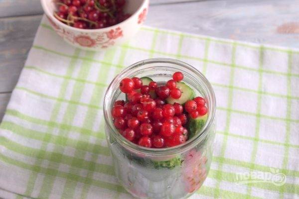Затем слейте воду. Добавьте промытые ягоды без веточек, а также измельчённый чеснок.