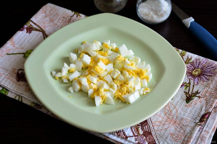 Куриные яйца отварите вкрутую и остудите. Нарежьте сваренные яйца кубиками.