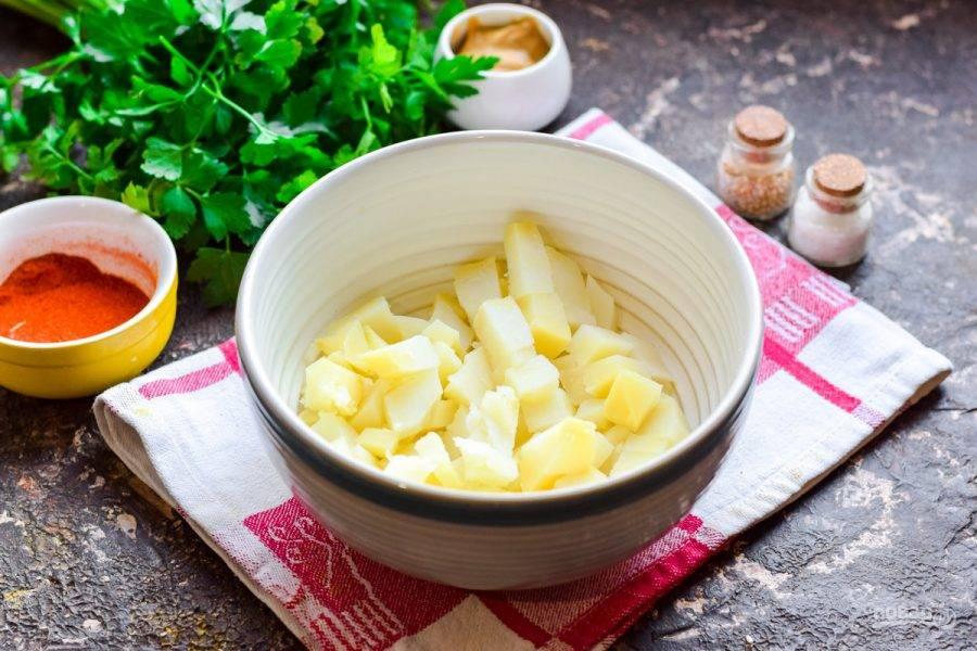 Отварите картофель, почистите и нарежьте небольшими кубиками. Переложите картофель в салатник.