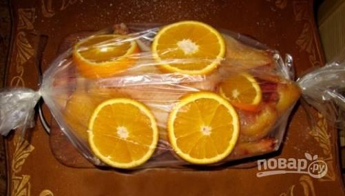 Натрите птицу солью внутри и снаружи. В утку поместите часть нарезанных апельсинов. Выложите тушку в рукав для запекания, а также положите несколько кружков апельсина. Рукав завяжите.