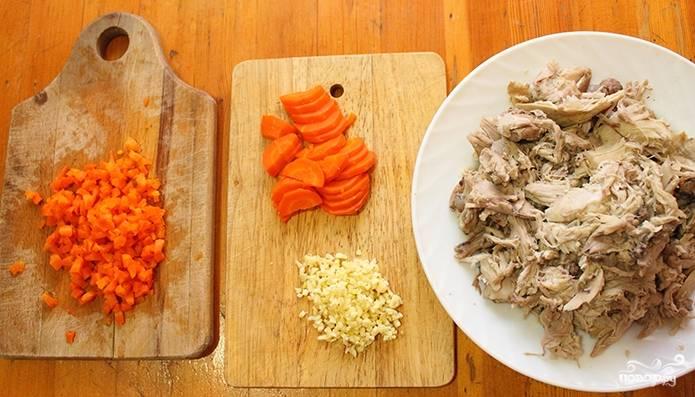 После того, как бульон будет готов, немного остудите его и процедите через кулинарное сито. Вареные овощи и чеснок порежьте. Мясо снимите с кости и помните вилкой, чтобы получились мелкие кусочки.