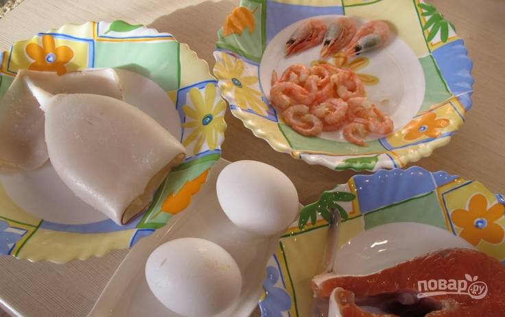 Очищенного кальмара промываем, а затем отвариваем в кипящей воде 2-3 минуты. Креветки также варим несколько минут, затем очищаем. Яйца варим вкрутую. Рыбку очищаем от кожи и нарезаем кусочками.
