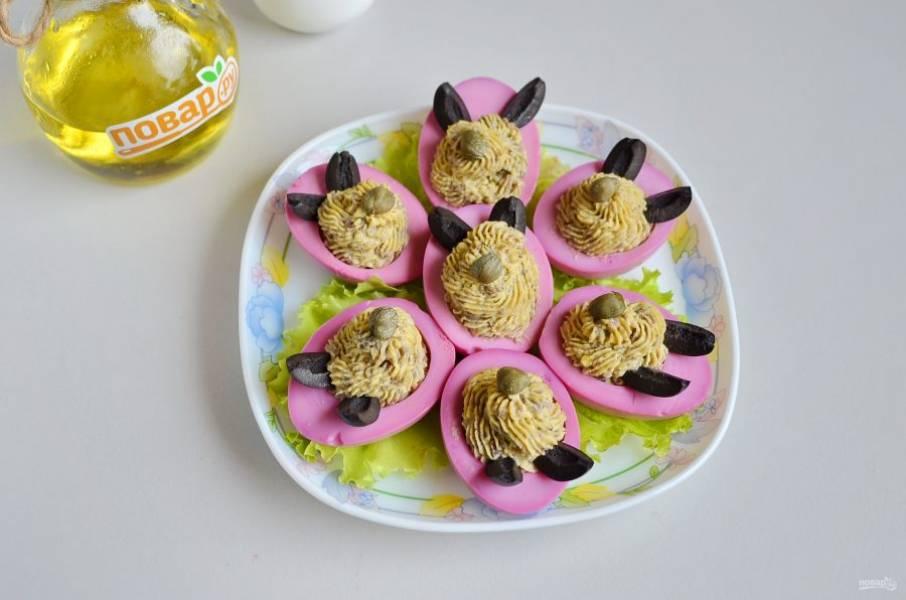 9. На тарелочку положите несколько листочков салата, разместите половинки яиц. Из оливок и каперсов сделайте мордашки.
