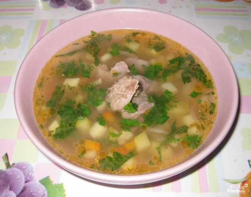В бульон выложите обжаренные овощи вместе с маслом, в котором они жарились. Также в кастрюлю положите томатную пасту, лавровый лист и перец. Нарубите петрушку, отправьте её в суп. Проварите всё ещё 10 минут — и подавайте суп, разлив его по тарелкам.