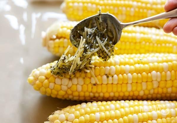 2. Полученную ароматную смесь выложите на кукурузу. Переместите на лист фольги, заверните плотным конвертом и отправьте на гриль.