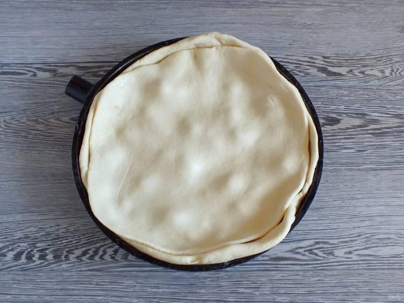 Раскатайте вторую часть теста в пласт и накройте ей яблочный слой.