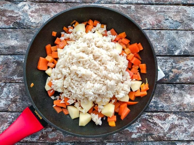Высыпьте полуготовый рис к тыкве с яблоком, перемешайте, налейте немного воды и тушите 15 минут.
