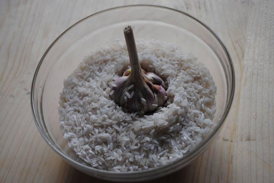 Замочите рис в холодной воде. Потом в мультиварку выложите головку чеснока целую.