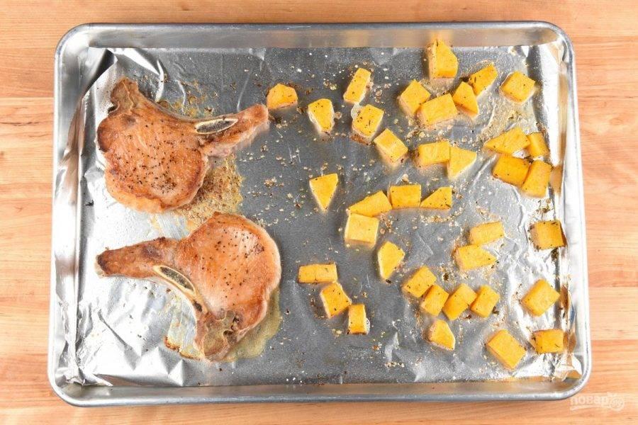 3. После этого кабачок переложите в большую сковороду. Влейте ещё масла и выложите отбивные. Обжарьте всё на среднем огне 10 минут, перевернув свинину 1 раз. Затем отбивные отправьте в духовку на 5 минут при 200 градусах.
