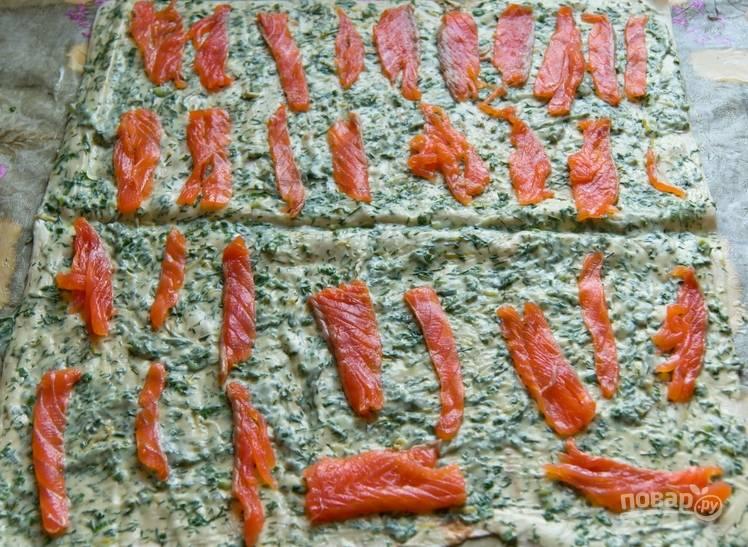 3. Смазываем лаваш сливочным сыром с зеленью. Равномерно раскладываем форель, присыпаем перцем и солью.