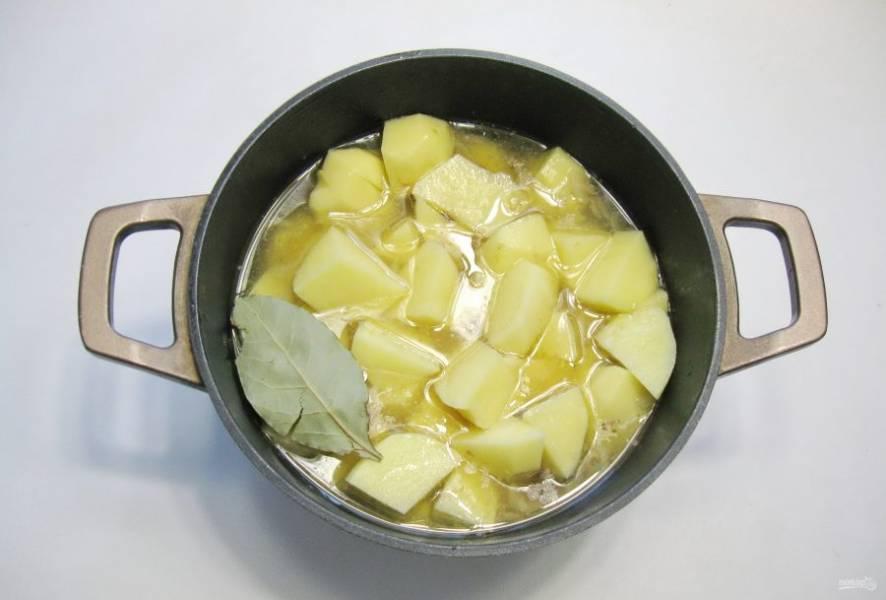 Картофель очистите, помойте и нарежьте кубиками. Добавьте в кастрюлю. Посолите и поперчите суп по вкусу, добавьте лавровый лист.
