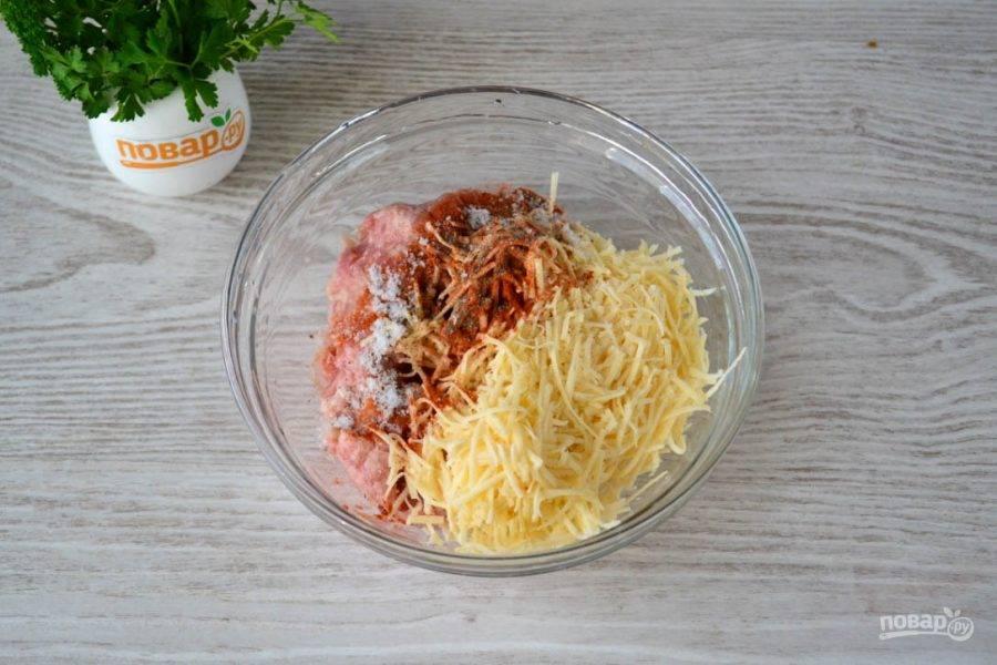 Фарш смешайте с натертым на мелкой терке твердым сыром, добавьте соль по вкусу, паприку и черный молотый перец.