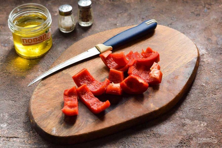 Сладкий перец очистите от семян и удалите перегородки. Нарежьте перец полосками.