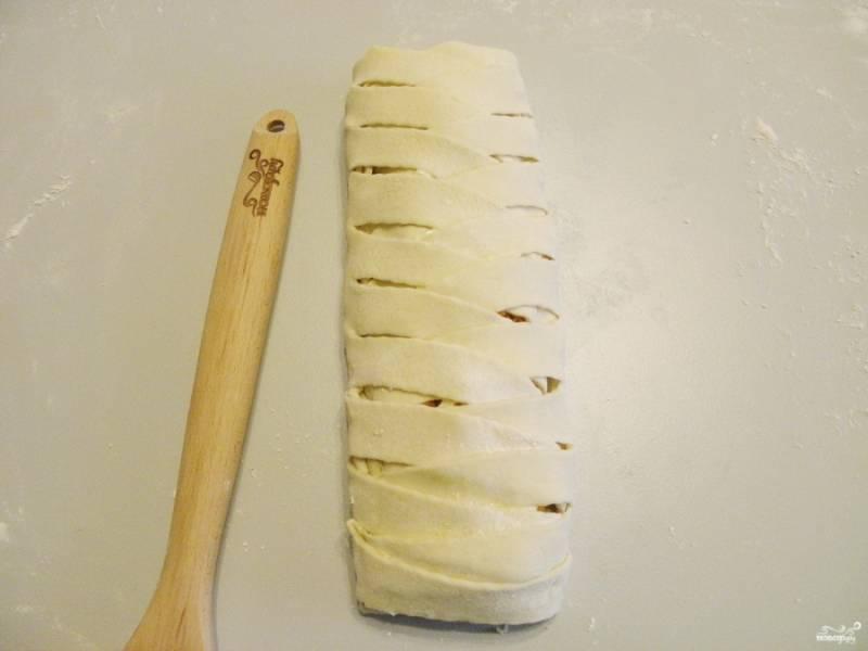 Посыпьте все тертым сыром и заплетите, как косичку, пирог. Края нужно вложить внутрь пирога.