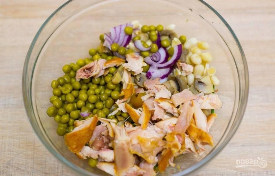 4.Болгарский перец мою и разрезаю, вычищаю от семян, а затем нарезаю кубиками. Копченую курицу нарезаю кусочками, лук нарезаю небольшими кусочками. В миску выкладываю измельченные ингредиенты, добавляю консервированный горошек и арахис в масле, измельченные грибы, зеленый лук.