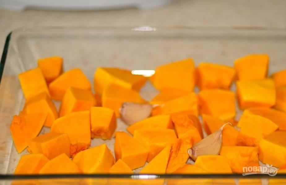 Тыкву вымойте, очистите и нарежьте на кусочки около трех сантиметров в диаметре. Выложите тыкву на противень, куда добавьте неочищенные зубчики чеснока. Полейте все оливковым маслом, посолите и поперчите по вкусу.