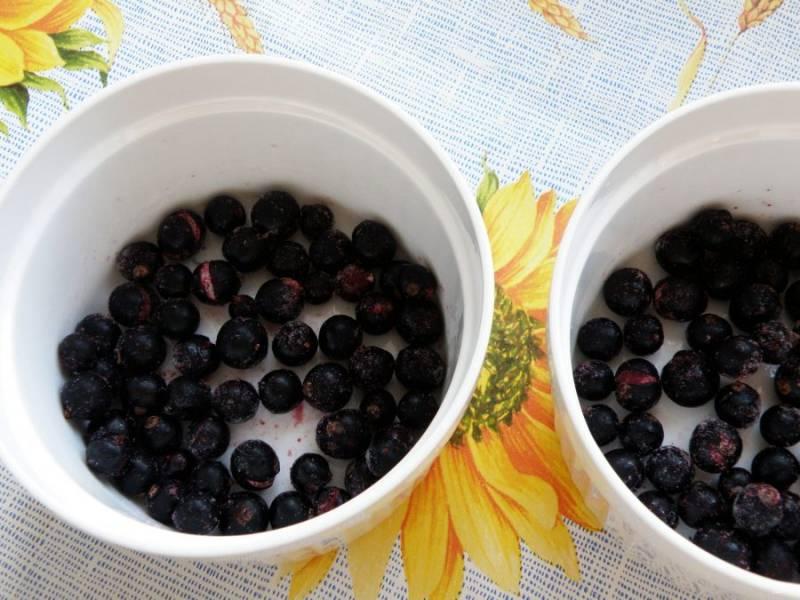 На дно керамических рамекенов выложите слой черной смородины.                                  Замороженную ягоду не размораживайте.