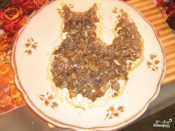 Нарежьте шампиньоны маленькими кусочками вместе с луком и потушите. Выложите третьим слоем на куриное филе.