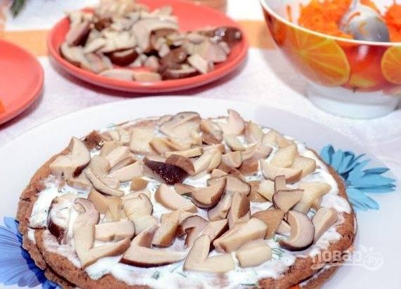 Далее выложите второй блин, соус и грибочки. Так чередуйте слои, пока ингредиенты не закончатся.