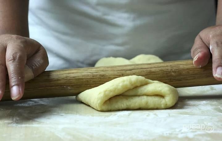 Теперь тесто вымесите руками и раскатайте в толстый пласт. Сложите в несколько раз и снова раскатайте.