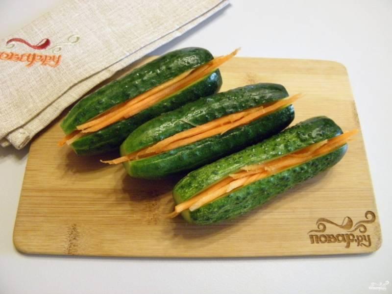 Очищенную морковь натрите на крупной терке. Каждый огурец надрежьте вдоль, не доходя до края, чтобы он не распался на половинки. Внутрь каждого огурчика вложите плотно морковь.