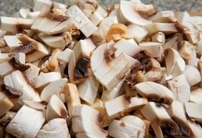 Итак, для начала промываем шампиньоны под проточной водой и сразу же после этого выкладываем их на кухонное бумажное полотенце, чтобы с них стекла лишняя жидкость. Теперь, поудобнее разместив ингредиент на разделочной доске, ножом удаляем огрубевшие хвостики и затем – нарезаем продукт на небольшие кусочки. Измельченные грибы выкладываем в чистую тарелку.