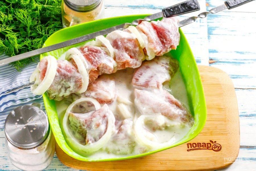 Спустя указанное время вы можете приступать к нанизыванию замаринованного мяса в кефире на шампура, чередуя мясные кусочки с луковыми кольцами.