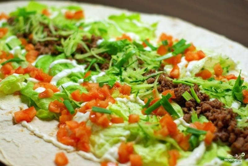 Поливаем майонезом и выкладываем мелко нарезанные помидоры и огурец. Посыпаем нарезанным зеленым луком и тертым сыром.